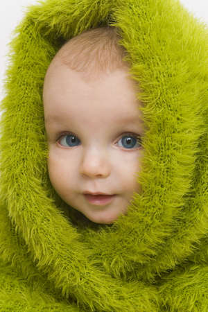 A blue eyed baby wrapped in a furry green blanket