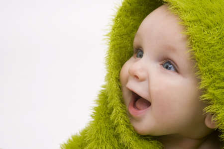 A beautiful smiling baby wrapped in a furry green blanket Stock Photo - 800559