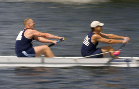 working hard: A motion blurred shot of a pair of rowers working hard to win a race