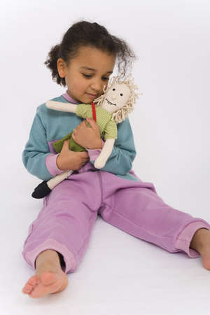romper: A beautiful mixed race girl playing with her favorite doll