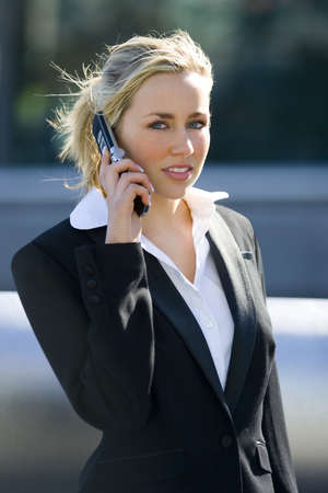 A beautiful young blonde female executive on her mobile phone in a hi tech landscape photo