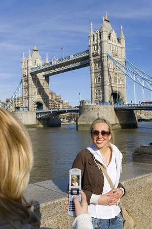 Una hermosa mujer joven ba�ado en la luz del sol de verano ha tenido su imagen en un tel�fono con c�mara delante de Tower Bridge, Londres, Inglaterra