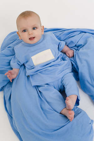 bedclothes: A young male baby dresssed in blue pyjamas laying back and relaxing on blue bedclothes