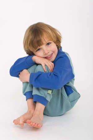 blonde boy: A cute little blonde boy dressed in a sleep suit and smiling for the camera Stock Photo