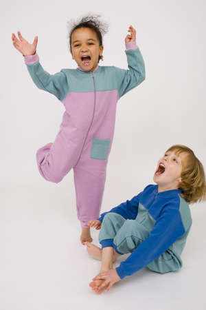 romper: Two young children, one a mixed race little girl the other a blonde boy, having great fun and laughing together.