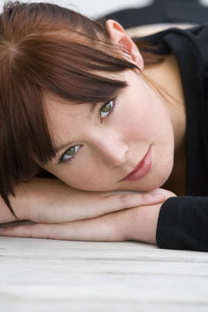 A beautiful young brunette woman laying down resting on her hands and looking enigmatically into the lens Stock Photo