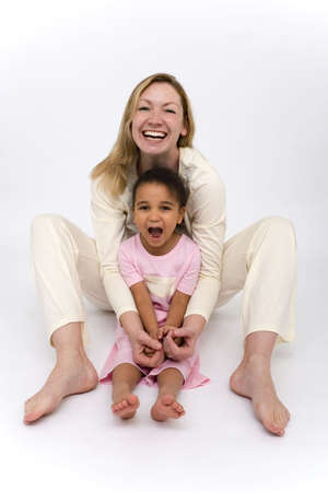 A mother and a beautiful little mixed race girl dressed in pajamas and having fun Stock Photo