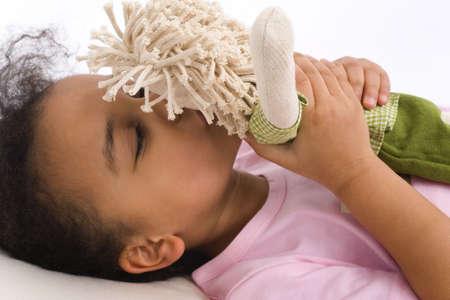 Une belle petite fille métisse située au lit et baiser sa poupée préférée  Banque d'images - 831037
