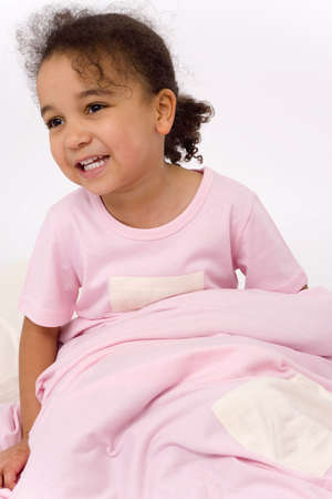 A beautiful little mixed race girl dressed in pink pajamas, sitting up in bed and smiling photo