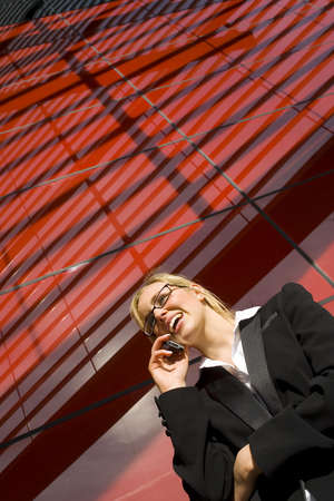 A beautiful young business woman talking on her phone in front of a hi tech office building photo