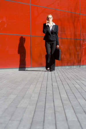A beautiful young business woman talking on her phone in front of a hi tech office building Stock Photo - 850885