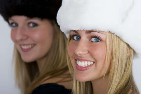 russian hat: Two beautiful Russian women wearing fur hats, shot in three quarter profile, one in focus one out but both smiling for the camera