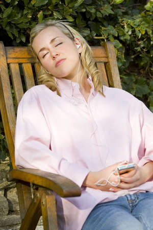 asleep chair: A beautiful young blonde woman sleeps in a garden chair, bathed in late evening sunshine and listening to her mp3 player Stock Photo