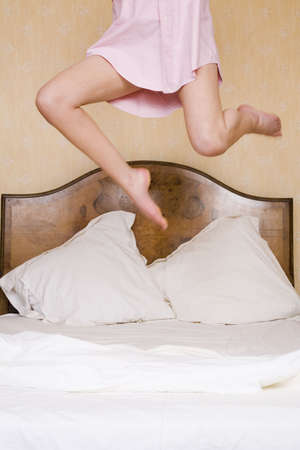 A young woman jumps excitedly on a double bed photo