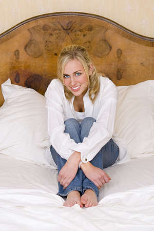 A stunningly beautiful blue eyed blonde haired young woman sitting on a double bed and smiling photo