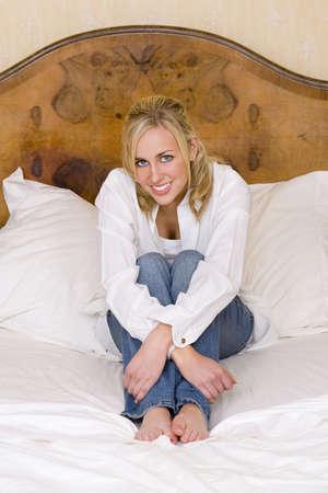 blue eyes blonde: Una mujer joven haired eyed azul imponentemente hermosa del blonde que se sienta en una cama matrimonial y que sonr�e