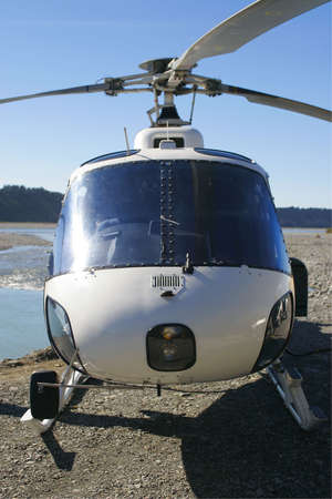 landed: A helicopter beside a blue river