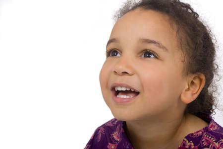 ni�os negros: Studio foto de una hermosa ni�a de raza mixta buscando skywards y sonriente. El fondo ha sido abandonado.