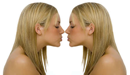 Mirrored shot of a gorgeous young blonde kissing...herself photo