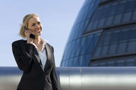 A beautiful young blonde executive using a mobile phone in a hi-tech surrounding. Stock Photo
