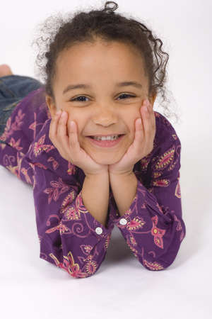 Studio shot of a beautiful mixed race little girl resting on her hands and smiling sweetly for the camera photo