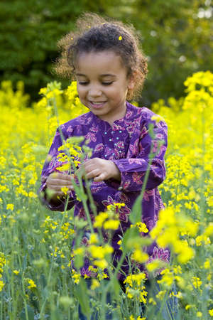 A beautiful mixed race girl looks having fun in a field full of yellow flowers photo