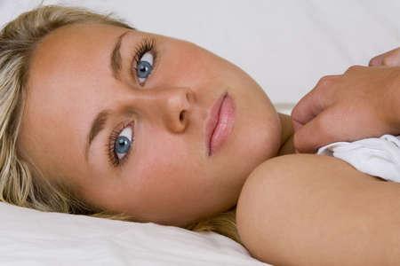 bedsheets: Studio tiro di un bel giovane biondo modello di ricerca rinfrescante bella sull'altro lato del letto