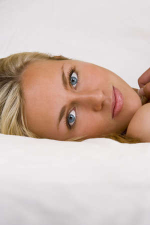 to other side: Studio shot of a beautiful young blond model looking refreshingly gorgeous on the other side of the bed Stock Photo