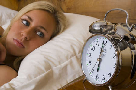 A beautiful young woman laying in bed watching her alarm clock Stock Photo - 932998