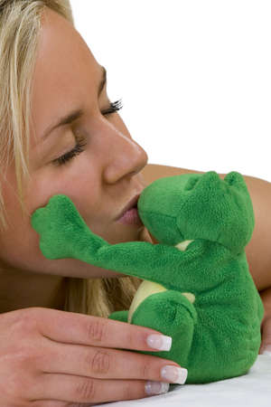caresses: A beautiful young blond woman laying on white bed sheets kisses a very lucky frog who gently caresses her cheek!