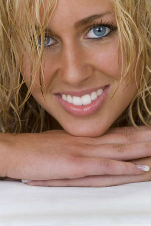 french manicure sexy woman: Close up studio shot of a stunningly beautiful young blonde woman with wet hair, bright blue eyes and a sexy smile
