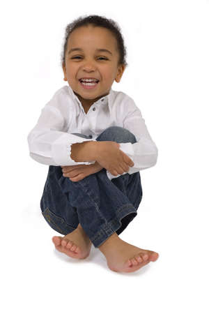 Isolated studio shot of a beautiful mixed race littkle girl sitting cross legged and laughing photo