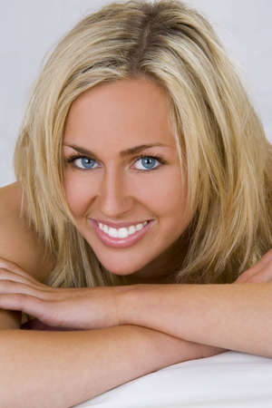 A stunningly beautiful young blond woman with bright blue eyes looking relaxed and happy