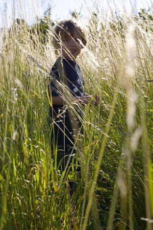 taller: A young boy backlit by evening sunlight walks through grass taller than him.
