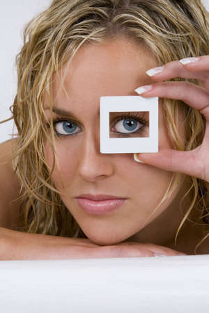 A stunningly beautiful young blond woman with bright blue eyes looking through a transparency frame photo