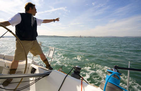 skipper: The skipper of a yacht points towards the horizon while keeping one hand on the boats wheel Stock Photo