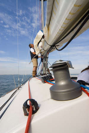 yachtsman: The skipper of a yacht adjusting his sails Stock Photo