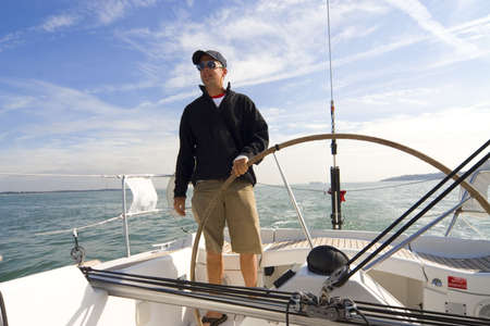 The skipper of a yacht takes the wheel Stock Photo