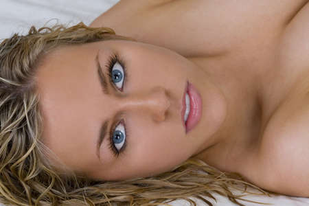cleavage: A stunningly beautiful young blond woman with bright blue eyes relaxing on a bed Stock Photo
