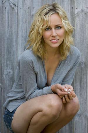 Un incre�blemente bella mujer joven rubia vestida casualmente en shorts y un top de color gris con capucha