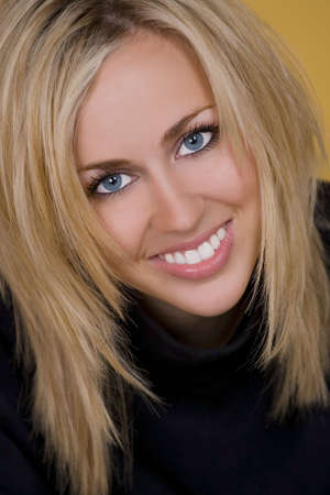 A stunningly beautiful young woman with blond hair and fantastic blue eyes smiling a gorgeous smile. photo