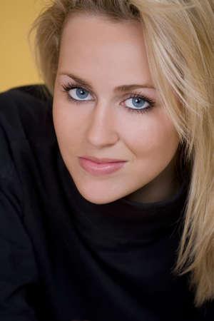 enigmatic: A stunningly bella giovane donna con capelli biondi e occhi blu fantastico sorridendo un enigmatico sorriso.