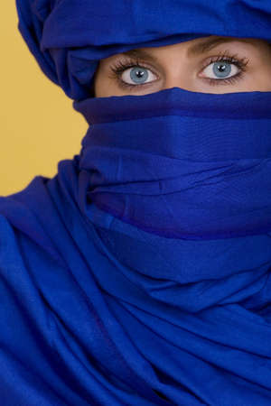 indigo: Beautiful blue eyes look out from behind an indigo veil Stock Photo