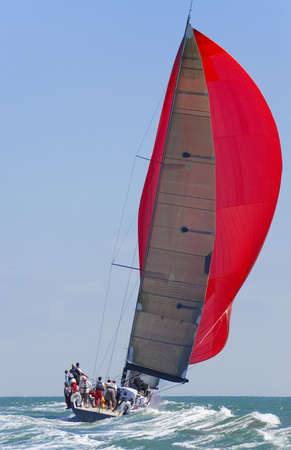 A fully crewed racing yacht with a red spinnaker catching the wind and leaving a big wake