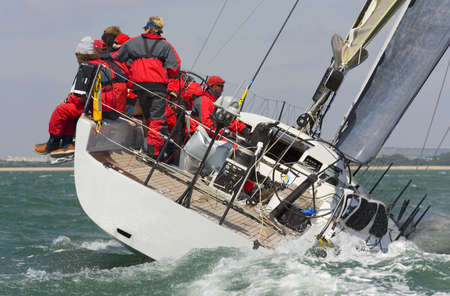 A fully crewed racing yacht racing hard and leaving a big wake