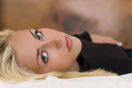 A gorgeous young blond woman with striking blue eyes laying down and looking thoughtfully into the lens.