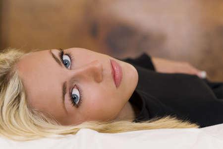 bionda occhi azzurri: Una splendida giovane donna bionda con gli occhi blu sorprendente, che stabilisce pensoso e guardando attraverso l'obiettivo.