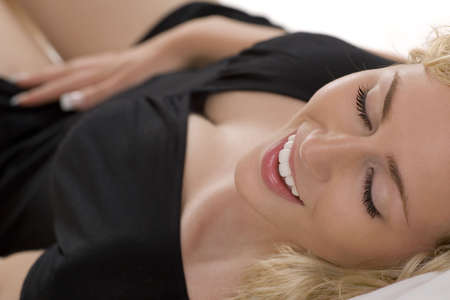 A beautiful young blond woman lying on her bed alone and happy photo