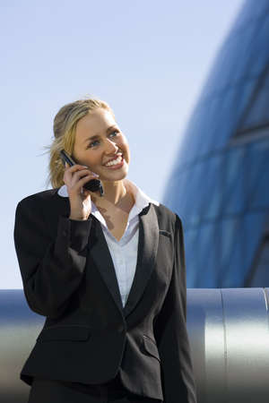 A beautiful young female executive using her mobile phone in a hi-tech urban setting photo