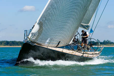 sails: A powerful black racing yacht with wind filled sails powers through coastal waters